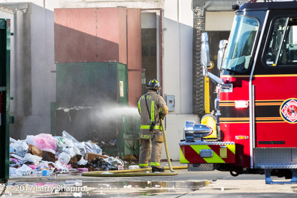 Firefighter with hose dousing dumpster fire