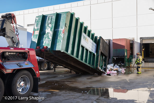 heavy wrecker lifts dumpster