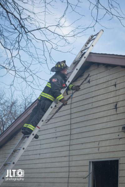 firefighter overhauls after house fire