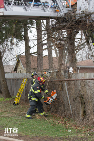 firefighter cuts vegetation along wooden fence