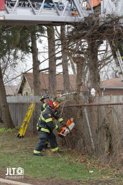 firefighter cuts vegetation along wooden fence