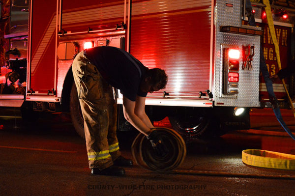 firefighter rolling hose after a fire