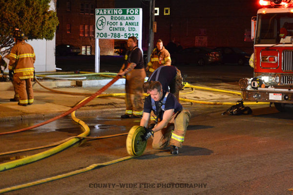 firefighters roll hose after a fire