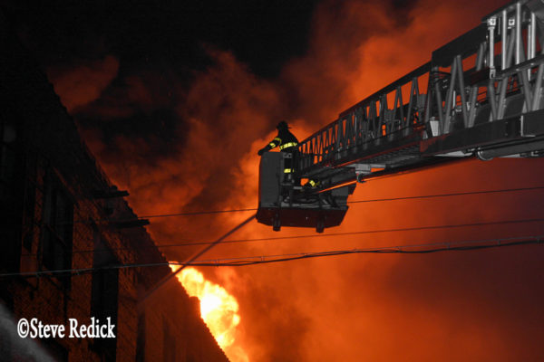 massive fire burns in warehouse at night