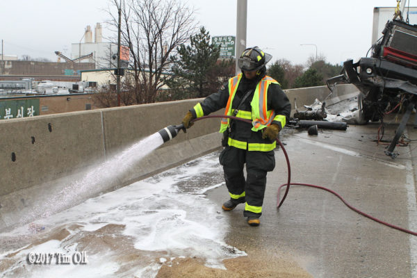firefighter applies foam after crash on highway
