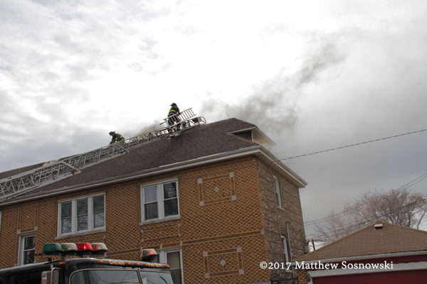 firefighters on peak roof to vent fire
