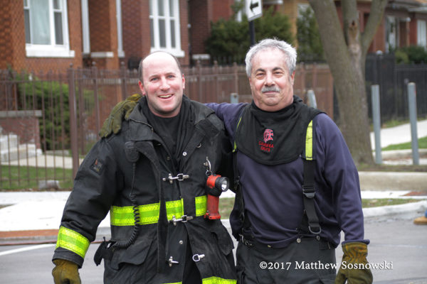 firefighters pose after battling a fire