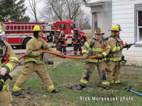 firefighters with hose line at fire