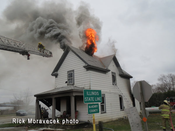flames burn the the roof of a house