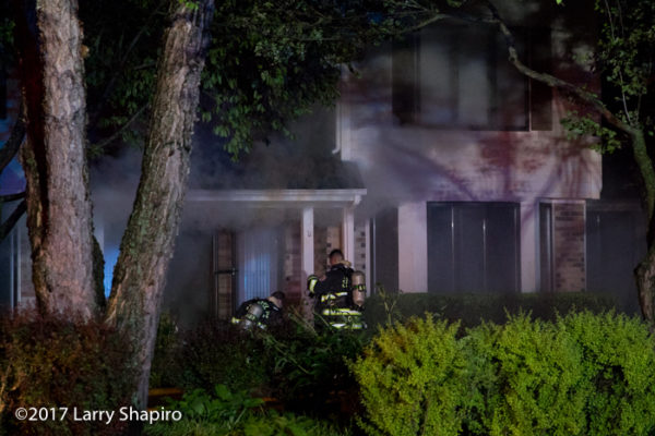 firefighters prepare to enter a house as heavy smoke pushes from basement fire