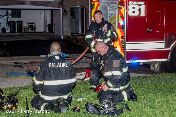 Firefighters rest after battling a blaze