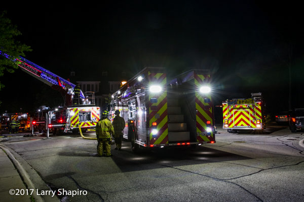 fire trucks with chevron striping on scene at night