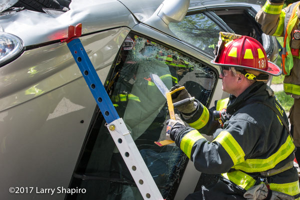 Firefighter cuts windshield of car