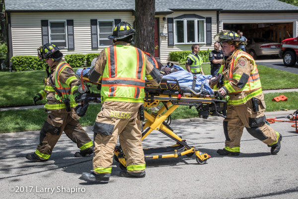 Firefighters move patient on Stryker cot
