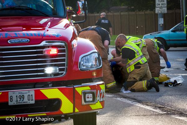 paramedics aid patient in street after crash