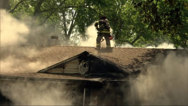 firefighters vent roof with heavy smoke