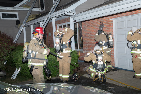 Firefighters prepare PPE before entering house on fire