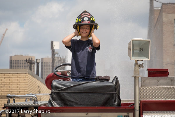 young boy on fire engine wearing a helmet