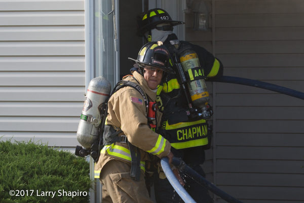 Firefighters guide hose line into a house