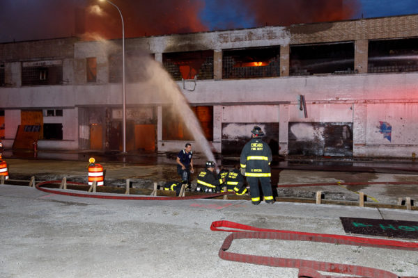firefighters with master stream at warehouse fire