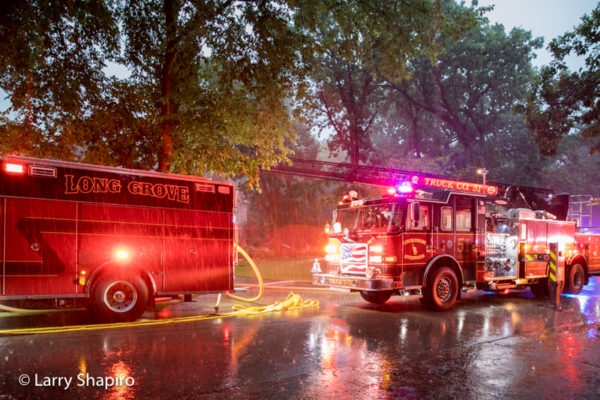 fire trucks at fire scene in driving rain