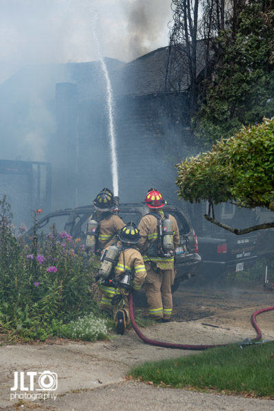 firefighters with hose line after house fire