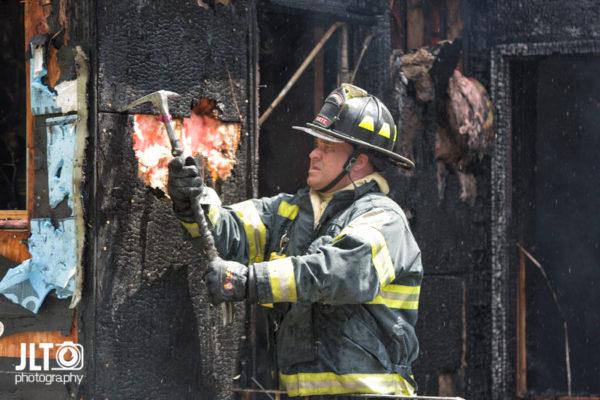 firefighter overhauls after a house fire