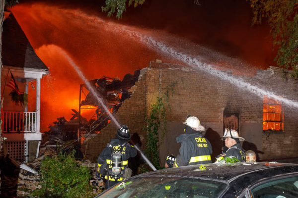 firefighters with master stream at fire