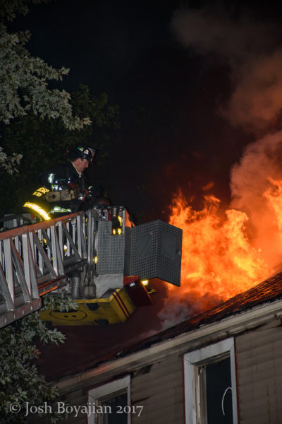 firefighter in tower ladder bucket against heavy fire