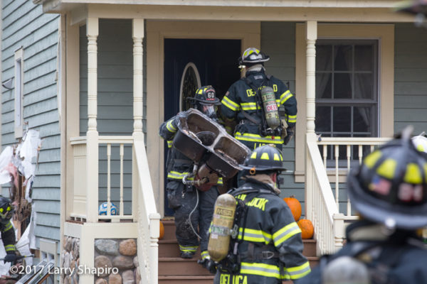firefighters remove debris after fire