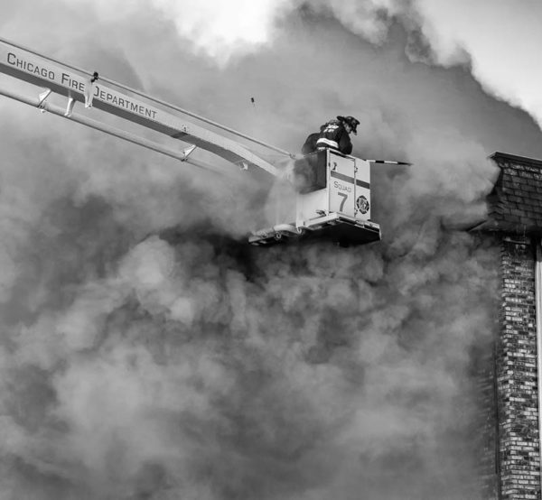 Chicago firefighters immersed in smoke at fire scene