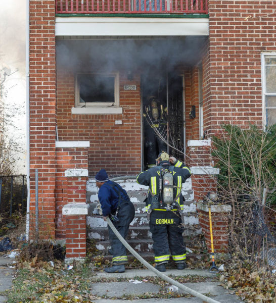 firefighters bring hose to door of house fire