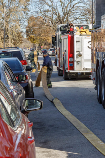 firefighters lay supply line in the street