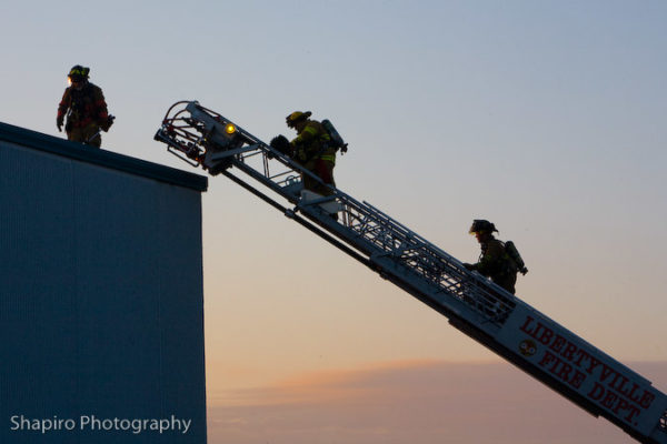firefighters climb aerial ladder against sunset