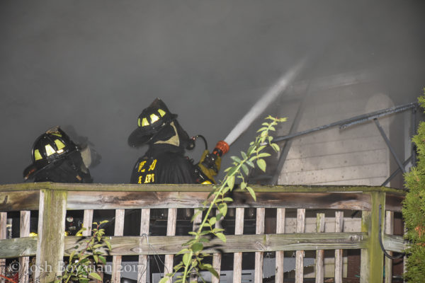 firefighter with hose at night fire scene