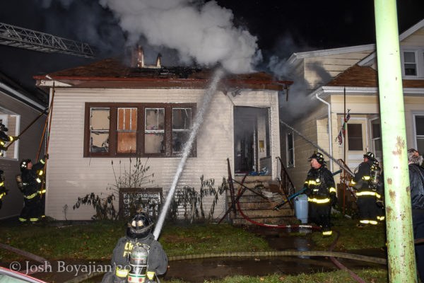 firefighter with hose line battles house fire at night