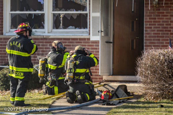 firefighters mask up before entering house