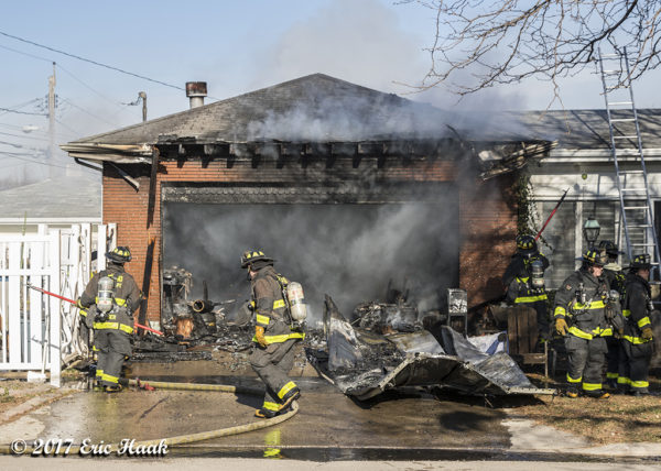 firefighters overhaul garage destroyed by fire