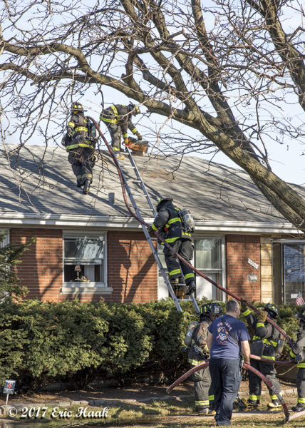 firefighters climb ladder to roof of a house