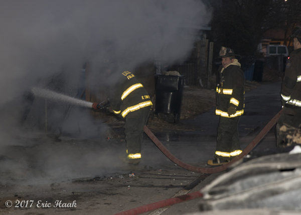 firefighters with hose line and smoke