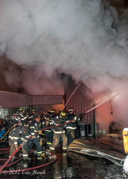 multiple firefighters handle large hoses