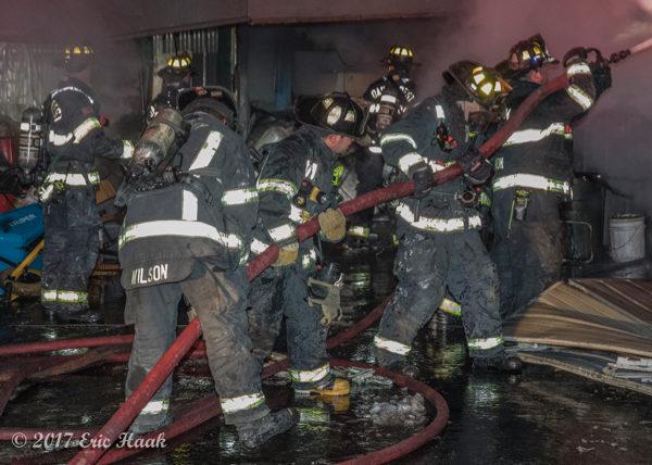 multiple firefighters handle large hose