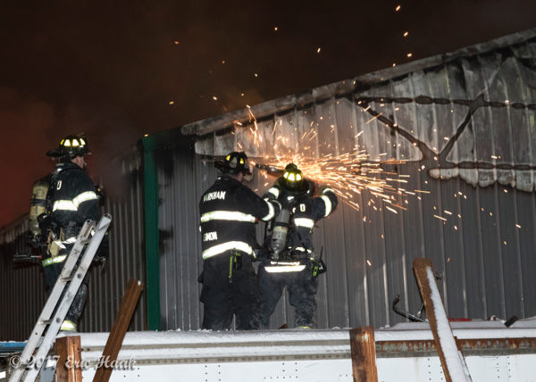 firefighters cut metal building with saw