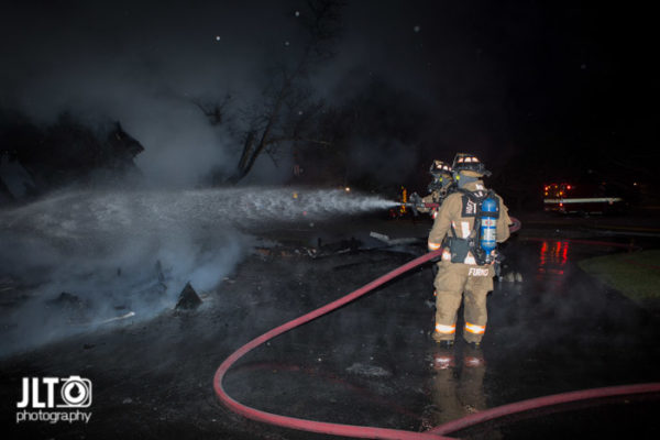 firefighters with hose line at night fire scene