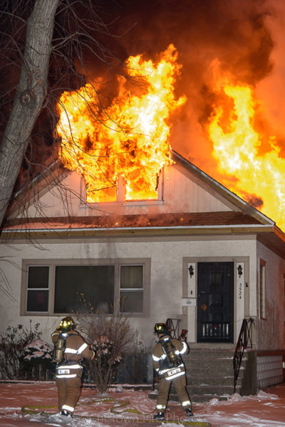 flames blowing out of house attic at night