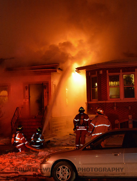 firefighters battle flames that engulfed a house at night