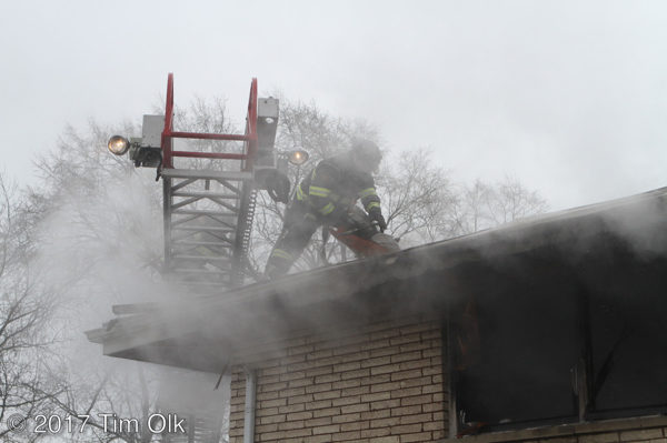 firefighter vents roof in smoke
