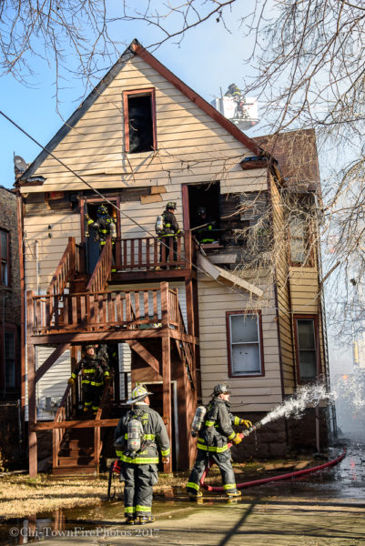 firefighters on back porch of two-flat