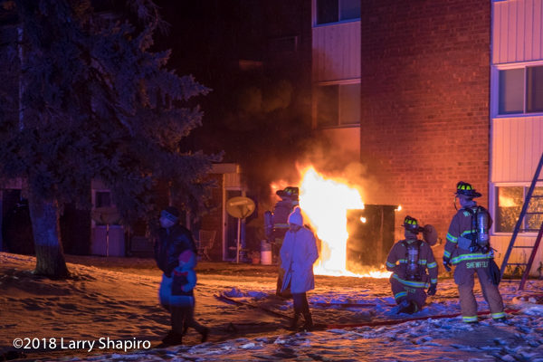 electric utility box engulfed in flames outside apartment building