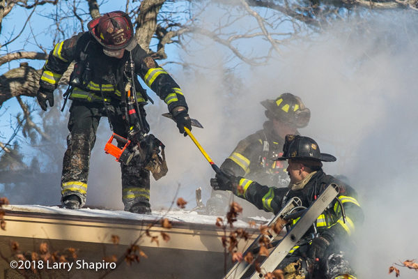 firefighter hands axe to another in roof with smoke